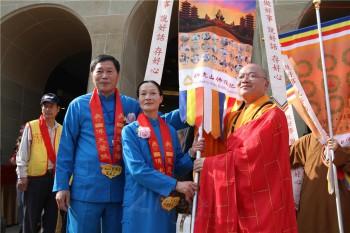 佛光山住持心保和尚頒發佛祖旗給松山慈惠堂堂主郭葉子。 圖/人間通訊社提供