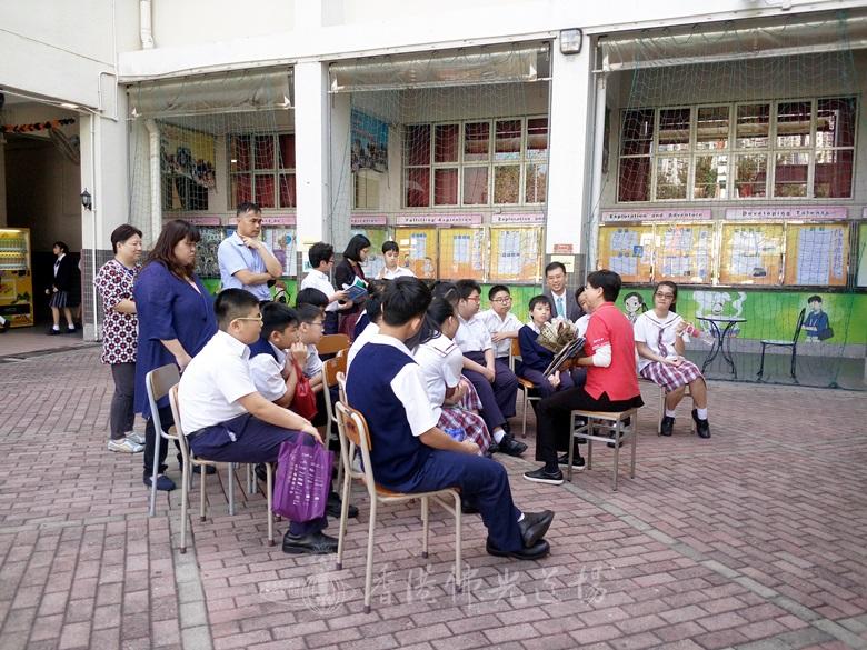 人間佛教讀書會義工配合書車出動,以立體書向佛教茂峰法師紀念中學同學敘述香港的故事,連陳校長也坐下來一起聆聽。
