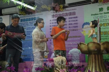 青年專注地浴佛,等候著的家人也正細心閱讀著浴佛單張[人間社記者陳樂賢攝]