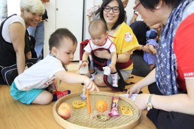 寶寶參與「抓周」,讓父母預測孩子未來的取向。(人間社記者黃偉強拍攝)