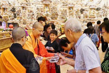 香港佛光道場住持永富法師親手派發結緣點心,目的讓大眾都能行到佛像前與佛接心,也令協助派發的大小工作人員感受到廣結善緣的喜悅。(攝影 黃慧莊)