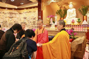 信眾恭敬地從香港佛光道場住持永富法師手上接過結緣壽飽。(人間社記者黃偉強拍攝)